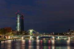 Το κτήριο EZB στη Φρανκφούρτη κατά τη διάρκεια της μπλε ώρας με μια αναμμένη γέφυρα στοκ εικόνες