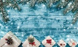 Το κυανό υπόβαθρο Χριστουγέννων με τα χειροποίητα δώρα και το έλατο διακλαδίζεται στην κορυφή της εικόνας Διάστημα για το κείμενο στοκ φωτογραφίες με δικαίωμα ελεύθερης χρήσης