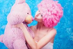 Το κωμικοί κορίτσι/η γυναίκα/ο έφηβος μπλε ματιών με τη ρόδινη σγουρή περούκα είναι ki Στοκ εικόνα με δικαίωμα ελεύθερης χρήσης