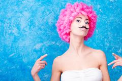 Το κωμικοί κορίτσι/η γυναίκα/ο έφηβος μπλε ματιών με τη ρόδινη σγουρή περούκα είναι εμείς Στοκ φωτογραφία με δικαίωμα ελεύθερης χρήσης