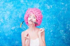Το κωμικοί κορίτσι/η γυναίκα/ο έφηβος μπλε ματιών με τη ρόδινη σγουρή περούκα είναι εμείς Στοκ φωτογραφίες με δικαίωμα ελεύθερης χρήσης