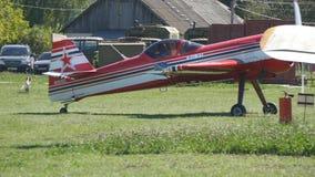 Το κόκκινο αθλητικό αεροπλάνο με τους γύρους προωστήρων πέρα από τον τομέα της πράσινης χλόης στον αερολιμένα κατά τη διάρκεια το απόθεμα βίντεο