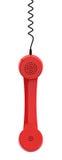 Το κόκκινο αναδρομικό επιχειρησιακό ακουστικό τηλεφώνου κρεμά από το σκοινί του στο άσπρο υπόβαθρο Στοκ φωτογραφία με δικαίωμα ελεύθερης χρήσης