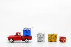 το κόκκινο αναδρομικό παιχνίδι αυτοκινήτων σκόρπισε τα κιβώτια με τα δώρα που απομονώθηκαν Στοκ εικόνα με δικαίωμα ελεύθερης χρήσης