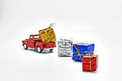 το κόκκινο αναδρομικό παιχνίδι αυτοκινήτων σκόρπισε τα κιβώτια με τα δώρα που απομονώθηκαν Στοκ Εικόνα