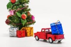 το κόκκινο αναδρομικό παιχνίδι αυτοκινήτων φέρνει ένα κιβώτιο με ένα δώρο για το χριστουγεννιάτικο δέντρο Στοκ Φωτογραφίες