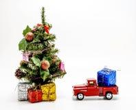 το κόκκινο αναδρομικό παιχνίδι αυτοκινήτων φέρνει ένα κιβώτιο με ένα δώρο για το χριστουγεννιάτικο δέντρο Στοκ Εικόνα