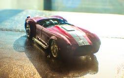 Το κόκκινο αυτοκίνητο αθλητικών παιχνιδιών κυλά το δρόμο ελαστικών αυτοκινήτου Στοκ εικόνες με δικαίωμα ελεύθερης χρήσης