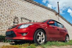 Το κόκκινο αυτοκίνητο στέκεται ενάντια σε έναν τουβλότοιχο Στοκ Φωτογραφία