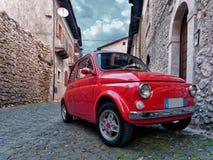 Το κόκκινο εκλεκτής ποιότητας αυτοκίνητο πόλεων στάθμευσε το παλαιό χωριό Στοκ φωτογραφία με δικαίωμα ελεύθερης χρήσης
