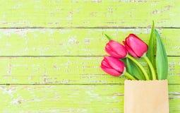 Το κόκκινο ελατήριο ανθίζει για το υπόβαθρο ημέρας βαλεντίνων ή ημέρας μητέρων, όμορφες τουλίπες στην τσάντα εγγράφου Στοκ Φωτογραφία