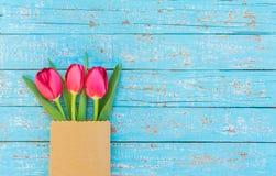 Το κόκκινο ελατήριο τουλιπών ανθίζει στην τσάντα εγγράφου στο ανοικτό μπλε ξύλινο υπόβαθρο για την ημέρα μητέρων ή βαλεντίνων Στοκ εικόνα με δικαίωμα ελεύθερης χρήσης