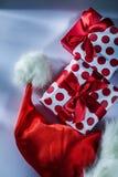 Το κόκκινο καπέλο Santa συσκεύασε το παρόν κιβώτιο στο άσπρο υπόβαθρο στοκ εικόνες