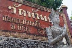 Το κόκκινο κείμενο της Ταϊλάνδης σημαδιών με την πέτρα και το μαρμάρινο γκρίζο άγαλμα προσεύχονται το CL Στοκ Εικόνες