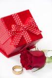 Το κόκκινο κιβώτιο δώρων με ένα κόκκινο αυξήθηκε και χρυσό δαχτυλίδι Στοκ Εικόνες