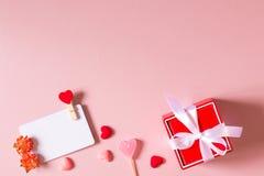Το κόκκινο κιβώτιο δώρων με το τόξο, πρότυπο καρτών πίστωσης/επίσκεψης με το σφιγκτήρα, άνοιξη ανθίζει, καραμέλα και μικρές καρδι Στοκ εικόνες με δικαίωμα ελεύθερης χρήσης