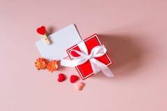 Το κόκκινο κιβώτιο δώρων με το τόξο, πρότυπο καρτών πίστωσης/επίσκεψης με το σφιγκτήρα, άνοιξη ανθίζει και μικρές καρδιές Στοκ Φωτογραφίες