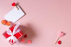 Το κόκκινο κιβώτιο δώρων με το τόξο, πρότυπο καρτών πίστωσης/επίσκεψης με το σφιγκτήρα, άνοιξη ανθίζει, καραμέλα και μικρές καρδι Στοκ Εικόνες