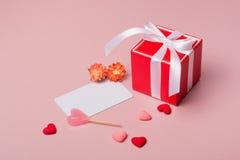 Το κόκκινο κιβώτιο δώρων με το τόξο, πρότυπο χαρτικών/φωτογραφιών, καραμέλα, άνοιξη ανθίζει και μικρές καρδιές Στοκ Εικόνα