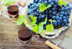 Το κόκκινο κρασί και τα σταφύλια στον τρύγο που θέτει με βουλώνουν Στοκ Φωτογραφία