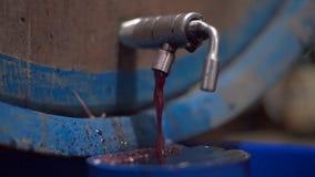 Το κόκκινο κρασί ρέει έξω από τη βρύση μιας δεξαμενής μέσα σε ένα κελάρι κρασιού φιλμ μικρού μήκους