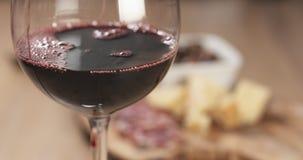 Το κόκκινο κρασί χύνει μπροστά από τα ιταλικά ορεκτικά antipasti Στοκ Εικόνα