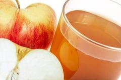 Το κόκκινο μήλο έκοψε το χυμό μήλων στο ποτήρι και τα φρέσκα μήλα σε ένα άσπρο υπόβαθρο Στοκ Εικόνα