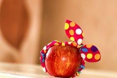 Το κόκκινο μήλο με ένα μεγάλο υπόβαθρο, ένα μήλο βρίσκεται σε έναν πίνακα, ένα μήλο σε έναν επίδεσμο, ένα αστείο μήλο, μινιμαλισμ στοκ εικόνες
