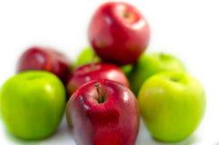 Το κόκκινο μήλο μεταξύ των μερών των πράσινων και κόκκινων μήλων απομόνωσε το άσπρο BA Στοκ Φωτογραφία