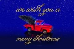 Το κόκκινο μικροσκοπικό εκλεκτής ποιότητας φορτηγό παραδίδει το χριστουγεννιάτικο δέντρο στην πλάτη του και το μήνυμα που σας ευχ Στοκ Φωτογραφία