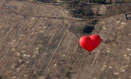 Το κόκκινο μπαλόνι με μορφή της κόκκινης καρδιάς αιωρείται πέρα από τον τομέα ως υπόβαθρο Στοκ φωτογραφία με δικαίωμα ελεύθερης χρήσης