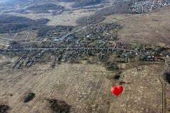 Το κόκκινο μπαλόνι με μορφή της κόκκινης καρδιάς αιωρείται πέρα από την έκταση - Στοκ εικόνα με δικαίωμα ελεύθερης χρήσης