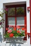 Το κόκκινο παράθυρο είναι διακοσμημένο με τα δοχεία του γερανιού στη Γαλλία Στοκ Εικόνα