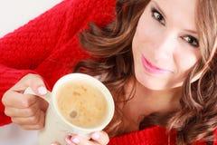 Το κόκκινο πουλόβερ κοριτσιών κρατά την κούπα με τον καφέ Στοκ Φωτογραφία