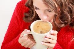 Το κόκκινο πουλόβερ κοριτσιών κρατά την κούπα με τον καφέ Στοκ Εικόνα