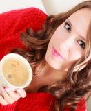 Το κόκκινο πουλόβερ κοριτσιών κρατά την κούπα με τον καφέ Στοκ Φωτογραφίες