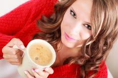 Το κόκκινο πουλόβερ κοριτσιών κρατά την κούπα με τον καφέ Στοκ εικόνες με δικαίωμα ελεύθερης χρήσης