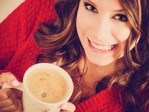 Το κόκκινο πουλόβερ κοριτσιών κρατά την κούπα με τον καφέ Στοκ Εικόνες