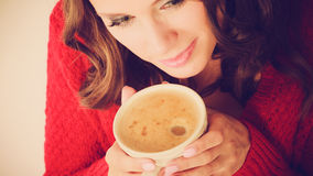 Το κόκκινο πουλόβερ κοριτσιών κρατά την κούπα με τον καφέ Στοκ φωτογραφία με δικαίωμα ελεύθερης χρήσης