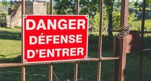 Το κόκκινο σημάδι που τοποθετείται σε μια σκουριασμένη πύλη ή αυτό γράφεται στο γαλλικό dange Στοκ εικόνες με δικαίωμα ελεύθερης χρήσης