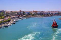 Το κόκκινο σκάφος πηγαίνει να ελλιμενίσει τη μαρίνα σε Menorca στην ακτή της Ισπανίας Στοκ Εικόνες