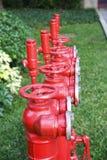 Το κόκκινο στόμιο υδροληψίας πυρκαγιάς, βάζει φωτιά στον κύριο σωλήνα, σωλήνας για την προσβολή του πυρός και πυροσβυστικός Στοκ Φωτογραφία