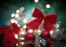 το κόκκινο σφαιρών κινηματογραφήσεων σε πρώτο πλάνο Χριστουγέννων υπόβαθρο γιρλαντών ντεκόρ ελαφρύ bokeh λάμπει ακτινοβολεί ανταν στοκ εικόνα