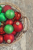 Το κόκκινο σφαιρών Χριστουγέννων, χρυσός, πράσινος, βρίσκεται σε μια ξύλινη κορυφή καλαθιών vie Στοκ Φωτογραφίες
