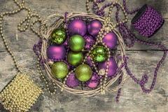 Το κόκκινο σφαιρών Χριστουγέννων, χρυσός, πράσινος, χάντρες βρίσκεται σε ένα ξύλινο καλάθι τ Στοκ εικόνες με δικαίωμα ελεύθερης χρήσης