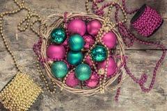 Το κόκκινο σφαιρών Χριστουγέννων, χρυσός, πράσινος, χάντρες βρίσκεται σε ένα ξύλινο καλάθι τ Στοκ Εικόνες