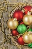 Το κόκκινο σφαιρών Χριστουγέννων, χρυσός, πράσινος, χάντρες βρίσκεται σε ένα ξύλινο καλάθι τ Στοκ Φωτογραφίες