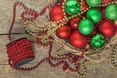 Το κόκκινο σφαιρών Χριστουγέννων, χρυσός, πράσινος, χάντρες βρίσκεται σε ένα ξύλινο καλάθι τ Στοκ εικόνα με δικαίωμα ελεύθερης χρήσης