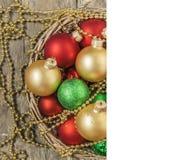 Το κόκκινο σφαιρών Χριστουγέννων, χρυσός, πράσινος, χάντρες βρίσκεται σε ένα ξύλινο καλάθι W Στοκ Εικόνες