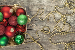 Το κόκκινο σφαιρών Χριστουγέννων, χρυσός, πράσινος, χάντρες βρίσκεται σε ένα ξύλινο καλάθι τ Στοκ Φωτογραφία